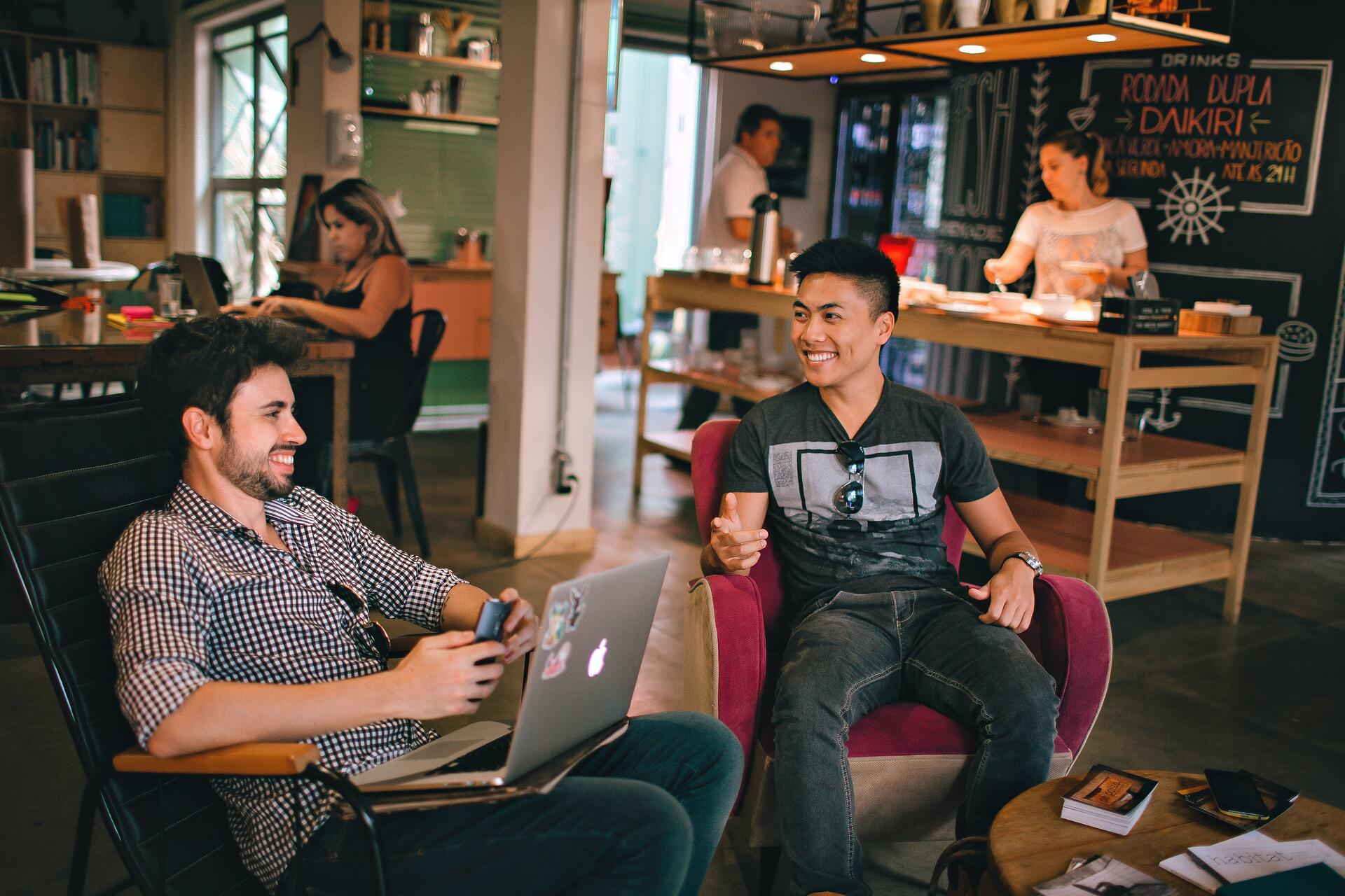 Two young men, one south Asian and one white, sit in a casual, artfully cluttered work space, smiling and talking about work.
